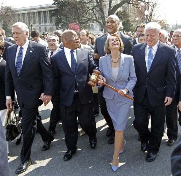 House Speaker Nancy Pelosi, holding the gavel used to pass the Medicare overhaul in 1965, walks to the Capitol with Democratic Reps. (from left) Steny Hoyer of Maryland, John Lewis of Georgia and John Larson of Connecticut after the passage of sweeping health care legislation. The procession took place through a throng of thousands of Tea Party activists protesting American Marxism and the passage of health care.