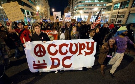 Coleson Breen, holding banner at left, marching during an Occupy D.C. action